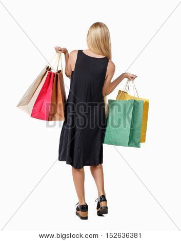back view woman with shopping bags . beautiful brunette girl in motion. backside view person. Rear view people collection. Isolated over white background. Long-haired blond girl holding shopping bags