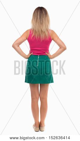 back view of standing young beautiful  woman.  girl  watching. Rear view people collection.  backside view of person.  Girl in green skirt standing with hands on waist.