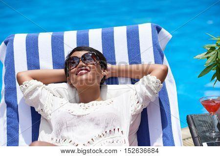 Asian smling young woman enjoying sunbathing by pool