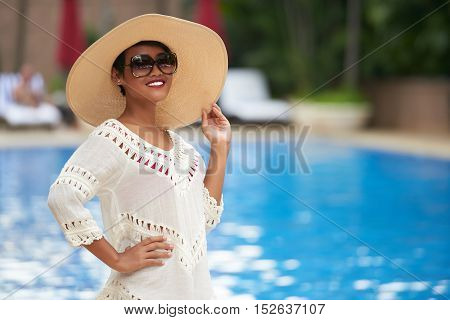 Portrait of beautiful woman in sunglasses and straw hat