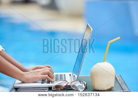 Hands of woman working on laptop during vacation