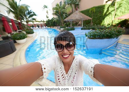 Happy woman taking selfie at spa resort