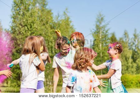 Group of happy kids having fun with colored powder outside