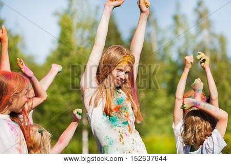 Happy young girl, smeared with colored powder, dancing on Holi color festival