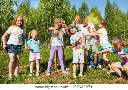 Happy kids having fun, celebrating color festival with colored powder on faces and body, outdoor in summer