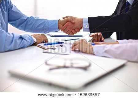 Business meeting at the table shaking hands conclusion of the contract.