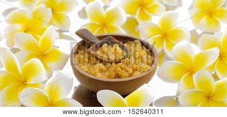 Pile of frangipani with salt in wooden bowl