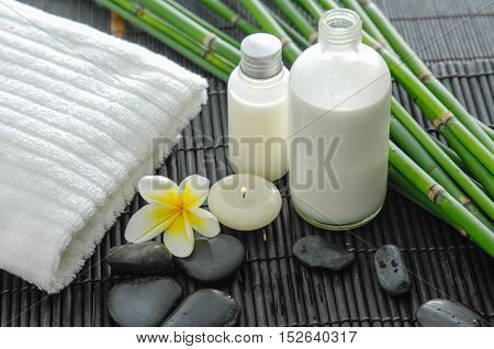 White towel and stones and flower ,grove,oil on bamboo mat