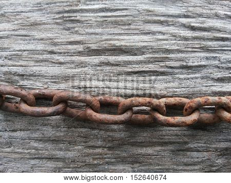 close up rusty chain on wood background