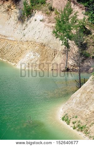 Beach of chalk quarry with turquoise water canyon and trees. Grodno, Belarus. Vertical view.
