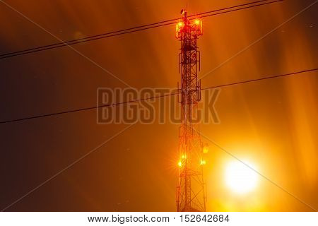 communications tower antenna night photo with a long exposure. yellow orange night sky version