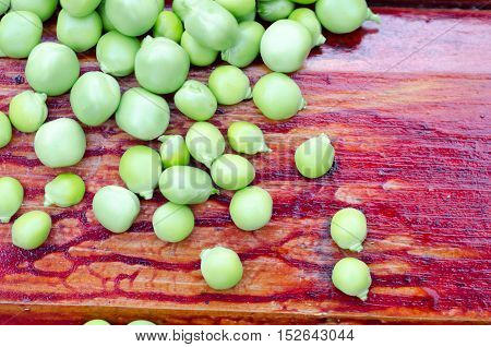 Fresh green peas on brown wooden background.