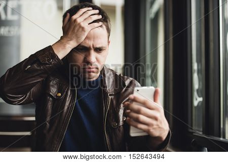 Bad news. Depressed young man expressing negativity while reading message on the mobile phone.