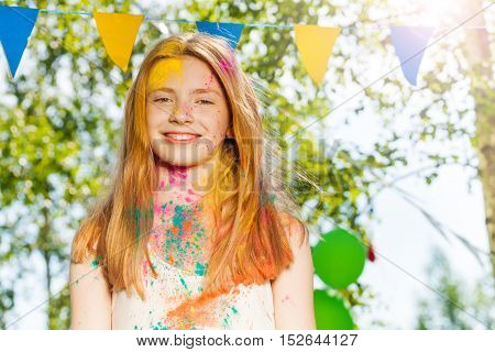 Portrait of happy young girl with face covered with colored powder on Holi color festival