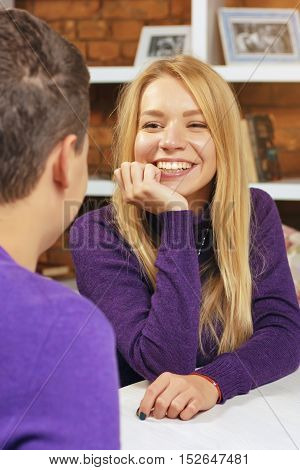 Girl smiling at the guy sitting in a cafe