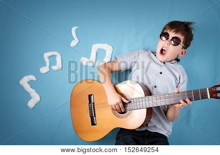 happy seven years old boy on blue blanket background with acoustic guitar and musical notes. Young guitarist singing song