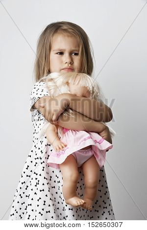 Adorable little girl cuddles and plays with her doll