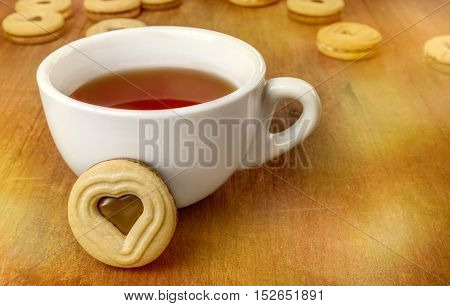 A white cup of tea and a butter cookie with a heart-shaped chocolate filling, on a dark wooden texture, more blurred cookies and bokehs in the background, with copyspace
