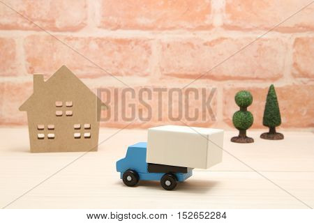 Toy car truck and house in front of brick wall.  Logistics, distribution, and delivery concept.