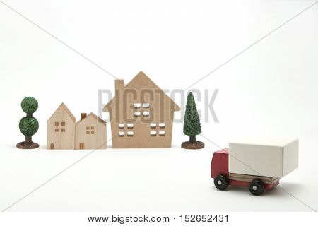 Toy car truck and houses on white background.  Logistics, distribution, and delivery concept.