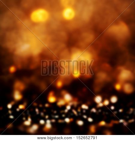 Golden Christmas shining glitter background with sparkling lights. Defocused gold abstract festive shimmer with copyspace