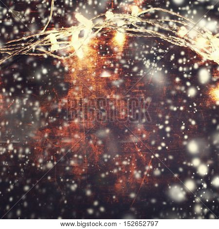 Beautiful abstract snowflake Christmas background with lights garland over wooden background with snowstorm