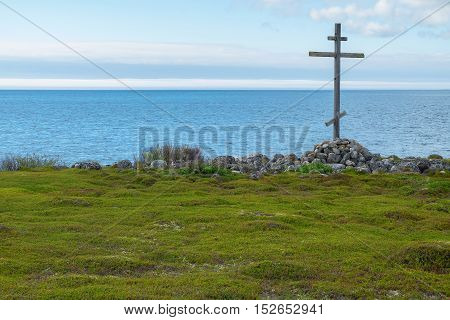 Wooden cross on the shores of the White Sea. Landscape religion history