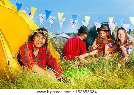 Portrait of smiling young man in chaplet sitting on the grass near his tent at hippy camping