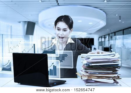 Young business woman looking virtual chart on the laptop with surprised expression while holding a pile of documents in the office