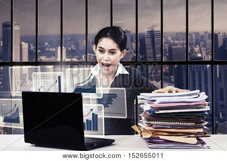 Businesswoman shocked in front of laptop while sitting in the office with a pile of document on the table