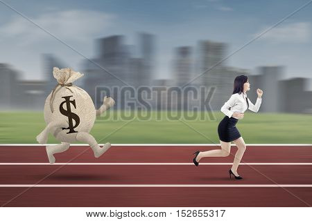 Young entrepreneur escaping from a bag of dollar while running on the track