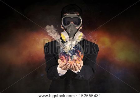 Image of young entrepreneur wearing gas mask while standing and holding a burning global earth in his hands