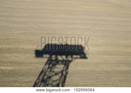 The Shadow Of A Water Tower On A Plowed Field