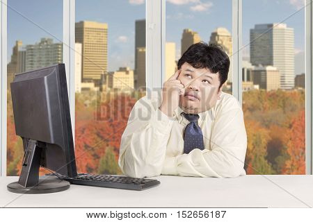 Obese businessman using computer and daydreaming while sitting in the office with autumn on the window