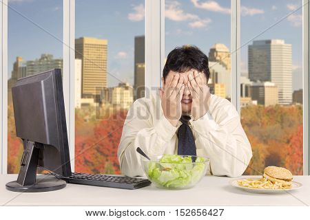 Overweight entrepreneur trying to diet while refusing temptation of food with autumn background on the window