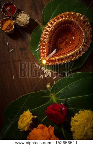 Indian puja set up and objects. Earthen lamp, fresh flowers and kumkum tilak. View fro top.