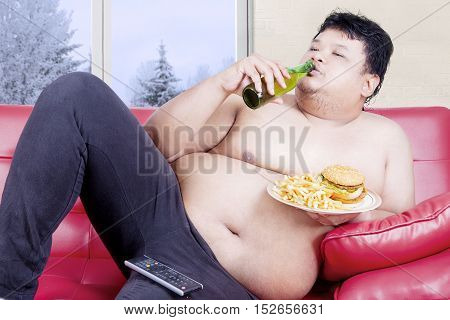 Image of an overweight man sitting on the red couch while drinking beer and eating junk food
