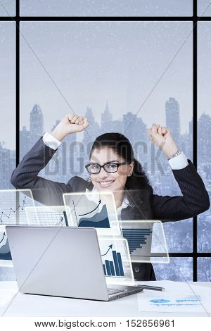Indian entrepreneur using laptop and sitting in the office while raising hands with happy expression