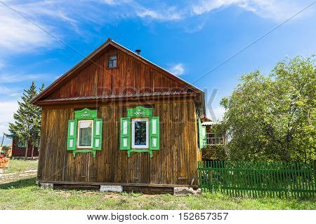 Beautiful wooden house with the green shutters stands on the outskirts of a Siberian village.