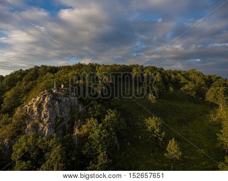 Rock Covered With Forest And Cloudy Sky.