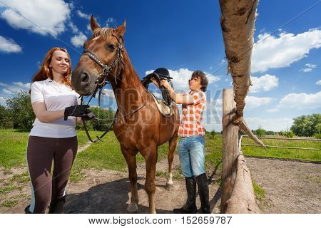 Portrait of young happy couple saddling their bay horse, standing next to the enclosure fence