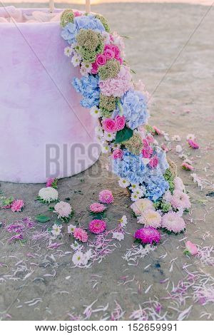 on the banks of wicker flower garland and petals with buds on the sand