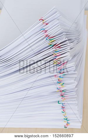Pile of overload document and reports place in horizontal with colorful paper clip on wooden table.
