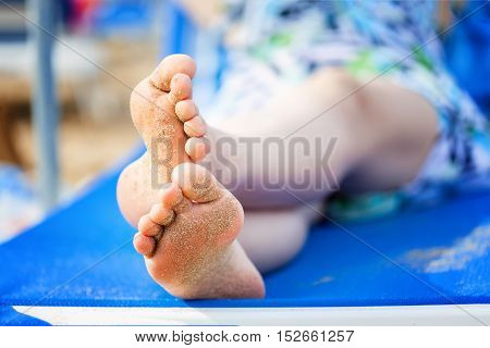 Legs of young woman lying on beach deck near the sea