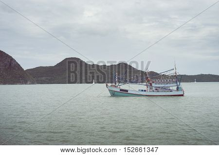 traditional fishing boat laying on the sea with big and long mountain in background.cloudy sky.filtered image.selective focus
