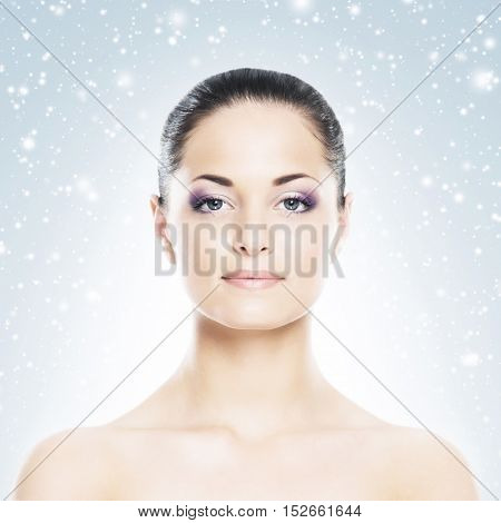 Spa portrait of young and beautiful woman over Christmas background. Face lifting and plastic surgery winter concept.