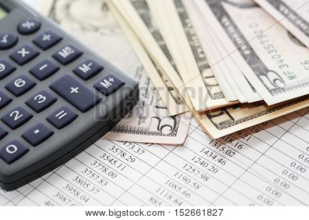 Calculator near money on paper background with digits