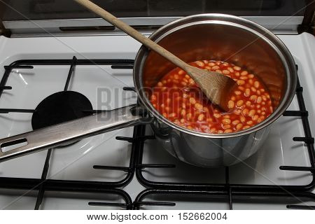 Saucepan Of Baked Beans Cooking On A Gas Oven Hob With Wooden Spoon