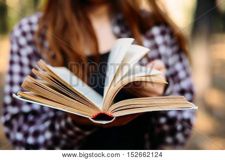 Hand Turning Pages Of A Book. Detail From A Woman Reading A Book