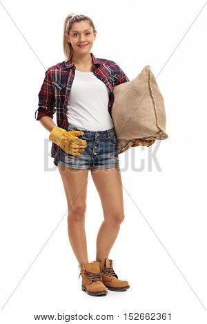 Full length portrait of a joyful female farmer holding a burlap sack isolated on white background